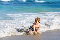 Kleiner blonder Kinderjunge, der Spaß auf Ozeanstrand in Florida hat Lizenzfreie Stockfotos