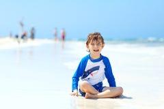 Kleiner blonder Kinderjunge, der Spaß auf tropischem Strand von Jamaika hat Lizenzfreies Stockfoto