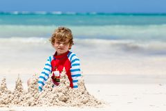 Kleiner blonder Kinderjunge, der Spaß auf tropischem Strand von Jamaika hat Stockbild