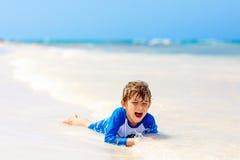 Kleiner blonder Kinderjunge, der Spaß auf tropischem Strand von Jamaika hat Lizenzfreie Stockbilder