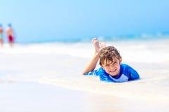 Kleiner blonder Kinderjunge, der Spaß auf tropischem Strand von Jamaika hat Stockbilder