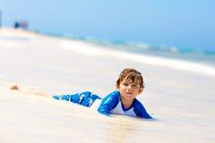 Kleiner blonder Kinderjunge, der Spaß auf tropischem Strand von Jamaika hat Lizenzfreies Stockbild