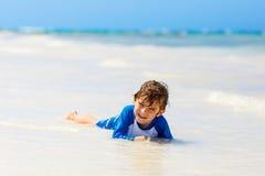 Kleiner blonder Kinderjunge, der Spaß auf tropischem Strand von Jamaika hat Stockfotos