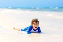 Kleiner blonder Kinderjunge, der Spaß auf tropischem Strand von Jamaika hat Lizenzfreie Stockfotografie