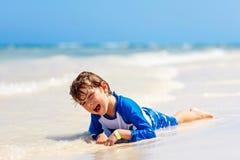Kleiner blonder Kinderjunge, der Spaß auf tropischem Strand von Malediven hat Stockbilder
