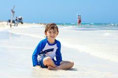 Kleiner blonder Kinderjunge, der Spaß auf tropischem Strand von Mexiko hat Stockbilder