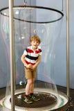 Kleiner blonder Kinderjunge, der zuhause mit enormem Seifenblasebau spielt Glückliches gesundes lächelndes Kind, das Spaß mit hat Stockbilder