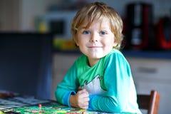 Kleiner blonder Kinderjunge, der zusammen zu Hause Brettspiel spielt Lustiges Kind, das Spaß hat Stockfotos