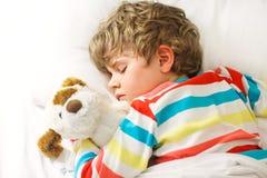 Kleiner blonder Kinderjunge im bunten Nachtzeug kleidet das Schlafen Stockfotografie