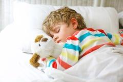 Kleiner blonder Kinderjunge im bunten Nachtzeug kleidet das Schlafen Stockbild