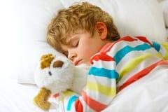 Kleiner blonder Kinderjunge im bunten Nachtzeug kleidet das Schlafen Lizenzfreie Stockfotos