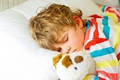 Kleiner blonder Kinderjunge im bunten Nachtzeug kleidet das Schlafen Stockbilder
