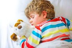 Kleiner blonder Kinderjunge im bunten Nachtzeug kleidet das Schlafen Lizenzfreie Stockfotografie