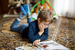 Kleiner blonder Kinderjunge mit Brillenlesebuch auf Boden zu Hause Stockfotografie