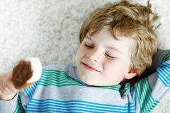 Kleiner blonder Kinderjunge mit den gelockten Haaren Eiscremeeis am stiel mit Schokolade zu Hause essend Stockfotografie