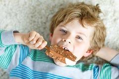 Kleiner blonder Kinderjunge mit den gelockten Haaren Eiscremeeis am stiel mit Schokolade zu Hause essend Lizenzfreies Stockfoto