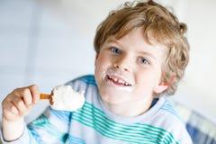 Kleiner blonder Kinderjunge mit den gelockten Haaren Eiscremeeis am stiel mit Schokolade zu Hause essend Lizenzfreie Stockfotografie