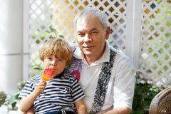 Kleiner blonder Kinderjunge und junger älterer Großvater, die zusammen Eiscreme im Sommer isst Stockfotos