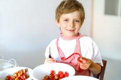 Kleiner blonder Kinderjunge, welche Erdbeermarmelade im Sommer hilft und macht Stockbild