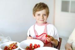 Kleiner blonder Kinderjunge, welche Erdbeermarmelade im Sommer hilft und macht Stockfoto