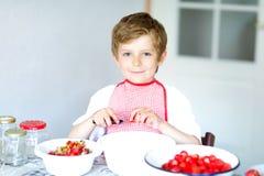 Kleiner blonder Kinderjunge, welche Erdbeermarmelade im Sommer hilft und macht Lizenzfreies Stockfoto