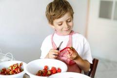Kleiner blonder Kinderjunge, welche Erdbeermarmelade im Sommer hilft und macht Lizenzfreie Stockfotografie