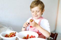 Kleiner blonder Kinderjunge, welche Erdbeermarmelade im Sommer hilft und macht Lizenzfreies Stockbild