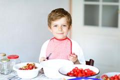 Kleiner blonder Kinderjunge, welche Erdbeermarmelade im Sommer hilft und macht Stockfotos