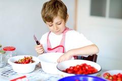 Kleiner blonder Kinderjunge, welche Erdbeermarmelade im Sommer hilft und macht Stockbilder