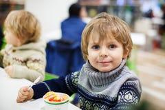 Kleiner blonder Kleinkindjunge, der Eiscreme iin Einkaufszentrum isst Stockbilder