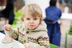 Kleiner blonder Kleinkindjunge, der Eiscreme isst Lizenzfreies Stockfoto