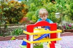 Kleiner blonder Kleinkindjunge, der mit Spielzeug - Parkplatzstation herein spielt Lizenzfreies Stockbild