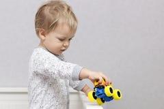 Kleiner blonder Kleinkindjunge, der mit Spielzeugauto spielt Kopieren Sie Platz Stockbilder