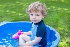 Kleiner blonder Kleinkindjunge, der mit Wasser im Sommer spielt Stockbilder