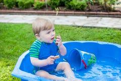 Kleiner blonder Kleinkindjunge, der mit Wasser im Sommer spielt Stockfoto