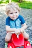 Kleiner blonder Kleinkindjunge, der rotes Spielzeugauto fährt Stockfotografie