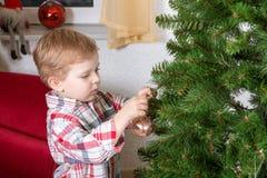 Kleiner blonder Kleinkindjunge, der zu Hause Weihnachtsbaum verziert Lizenzfreies Stockfoto