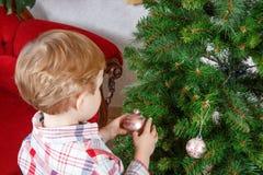 Kleiner blonder Kleinkindjunge, der zu Hause Weihnachtsbaum verziert Stockfoto