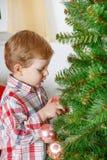 Kleiner blonder Kleinkindjunge, der zu Hause Weihnachtsbaum verziert Lizenzfreie Stockbilder