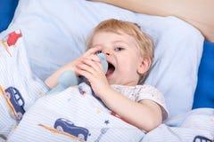 Kleiner blonder Kleinkindjunge im Bett Stockbilder