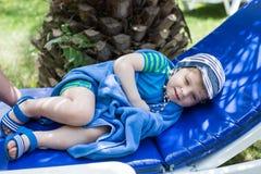 Kleiner blonder Kleinkindjunge in swimm Klage auf Couch Stockbild