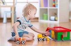 Kleiner blonder Kleinkindkinderjunge spielt mit Spielzeugauto Stockbilder
