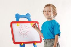 Kleiner blonder lächelnder Junge zeichnete eine Sonne auf whiteboard Lizenzfreie Stockbilder