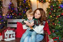 Kleiner blonder reizend Junge sitzt auf dem Schoss der Mutter und des Schlages Lizenzfreies Stockbild