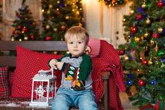 Kleiner blonder reizend Junge sitzt auf einer Bank und dem Halten einer Laterne lizenzfreies stockbild