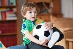 Kleiner blonder Vorschuljunge von 4 Jahren mit dem Fußball, der socc schaut Stockfoto