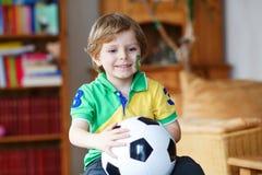 Kleiner blonder Vorschuljunge von 4 Jahren mit dem Fußball, der socc schaut Lizenzfreie Stockfotos