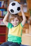 Kleiner blonder Vorschuljunge von 4 Jahren mit dem Fußball, der socc schaut Stockbilder