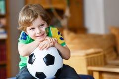 Kleiner blonder Vorschuljunge von 4 Jahren mit dem Fußball, der socc schaut Stockbild
