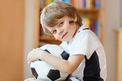 Kleiner blonder Vorschulkinderjunge mit Fußballfußball-Cupspiel des Balls aufpassendem im Fernsehen Lizenzfreie Stockfotos
